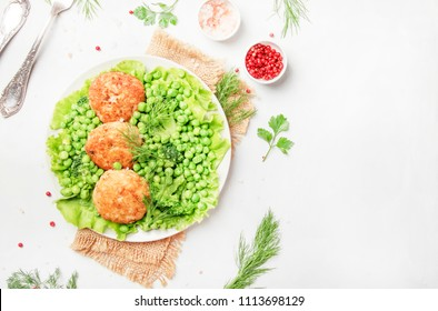Fish meatballs or cutlets from sea cod with green vegetables, top view