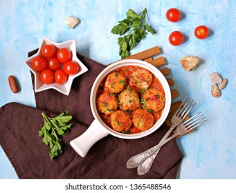 Fish meatballs in tomato sauce in a white ceramic pan on a light blue concrete background. Top view, copy space.