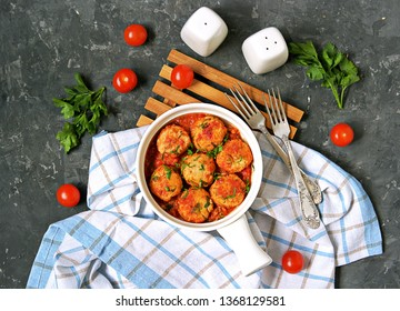 Fish meatballs in tomato sauce in a white ceramic pan on a dark concrete background. Top view. Seafood.