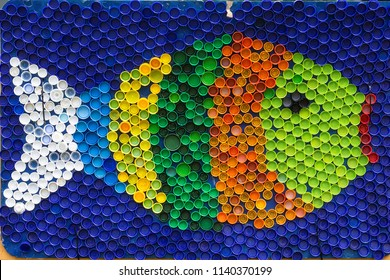 Fish mosaic deocoration made of cororful plastic bottle caps . Summer season and travel concept. Handmade crafts. Recycling art.