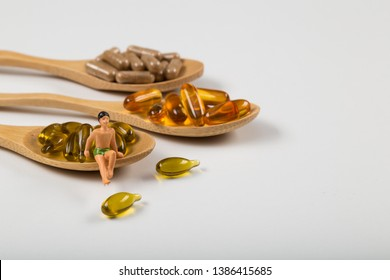 Fish oil capsules against diseases in a wooden spoon on white background, omega 3 and vitamin B,C,D healthy diet concept.
