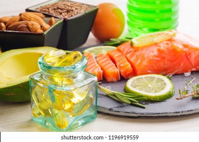 Fish oil capsules and food Omega 3 sources - piece of fish, avocado, nuts, linen seeds, egg