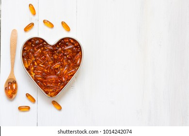 Fish oil capsules in a heart shape plate on white wooden background and texture, vitamin D supplement, selective focus