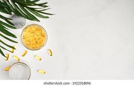 Fish oil capsules with omega 3 and vitamin D in a glass jar on a white concrete table top view, healthy eating concept. Cod liver oil softgels, layout with copy space