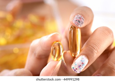 Fish oil capsules pills and human hand (Woman people)