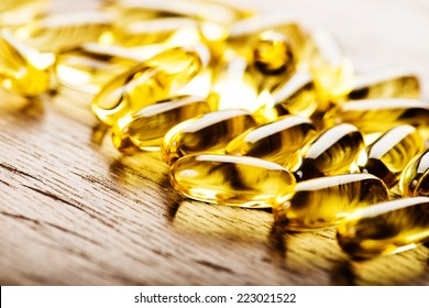 Fish oil omega 3 gel capsules isolated on wooden background