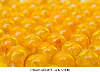 Fish oil OMEGA3 DHA EPA in yellow soft gelatin capsules pills arrange to be fish shape isolate on white background with copy space for text. gelatinous capsule fish fat