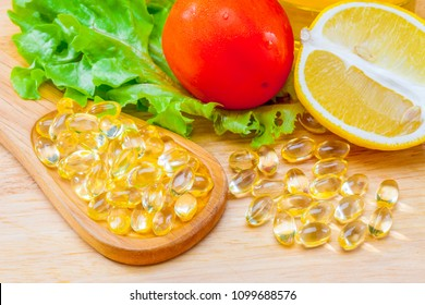 Fish oil, soft capsule, omega 3, supplement food vitamin D capsules with vegetables and fruit greens tomato lemon on wood . still life of healthy food and supplementary  diet concept