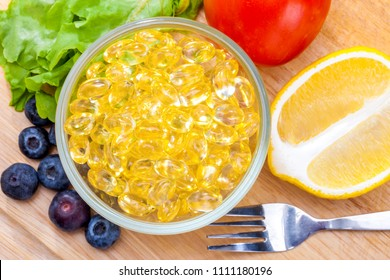 Fish oil, soft capsule, omega 3, supplement food vitamin D capsules with vegetables and fruit greens tomato lemon blueberry on wood . still life of healthy food and supplementary  diet concept