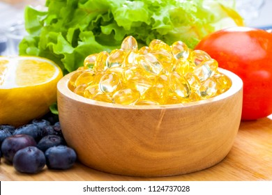 Fish oil, soft capsule, omega 3, supplement food vitamin D capsules with vegetables and fruit greens tomato lemon blueberry on wood .still life of healthy food and supplementary  diet concept closeup