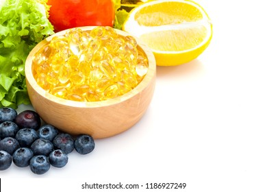 Fish oil, soft capsule, omega 3, supplement food vitamin D capsules with vegetables and fruit greens tomato lemon blueberry on white background .still life of healthy food and supplementary  diet