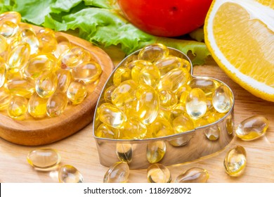 Fish oil, soft capsule, omega 3, supplement food vitamin D capsules in Heart shaped  with vegetables and fruit greens tomato lemon on wood . still life of healthy food and supplementary  diet concept