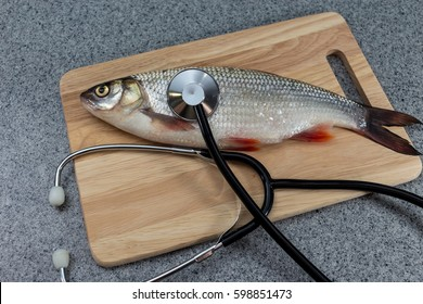 Fish on a cutting Board, lying next to a stethoscope The doctors recommend Symbolizes allergic to fish or artificiality of food or the risk of infection when consuming fish. The need for medical care.