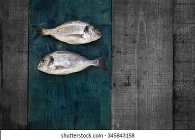 fish  on a green rustic wooden floor - Goldfish, sea bream, Gilt-head bream, Sparidae