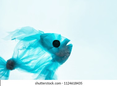 Fish from a plastic bag. Blue color, translucent. The concept of saving the environment, pollution of the oceans, seas and rivers. White background for copy space text