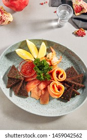 Fish platter with light-salted salmon, smoked salmon, red caviar and Borodino triangular black bread toast with green parsley top view. Delicacy fresh seafood sashimi dish with sliced trout