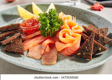 Fish platter with light-salted salmon, smoked salmon, red caviar and Borodino triangular black bread toast with green parsley close up. Delicacy fresh seafood sashimi dish with sliced trout