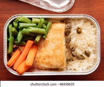 Fish and rice - inflight meal, shot on wooden surface