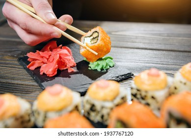 fish roll held with chopsticks close-up. Roll hiccup in wasabi.