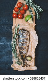 Fish with rosemary and lime on parchment paper on a black wooden background
