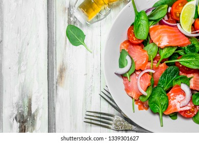 Fish salad. Salad with slices of salmon, tomatoes and spinach with lime juice. On a rustic background.