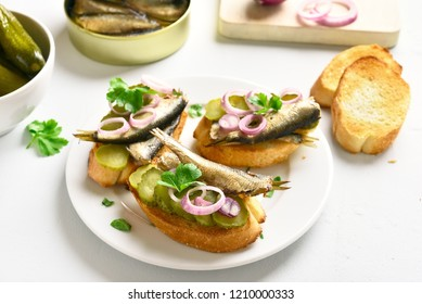 Fish sandwiches with sprats, marinated cucumber and onion. Tasty snack