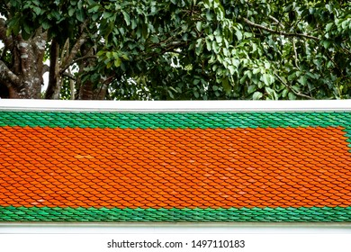 Fish scale pattern roof tiles in vibrant green and orange colors. Roof shingles against green foliage of big tree.