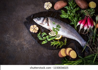 fish sea bass with vegetables potatoes, garlic and herbs, ingredients for cooking