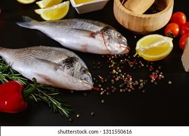 Fish seafood dorado, raw food on black background with ice,  lemon.