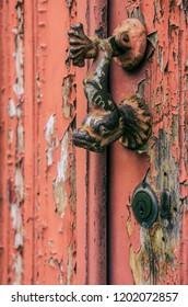 Fish shaped door knocker on an old wooden door with red peeling paint