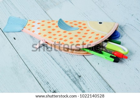 Fish shaped pencil case on wooden background.