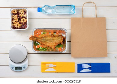 Fish with sliced carrot and arugula, nuts and dried fruit, a food scale, a bottle of water, plastic flatware and a paper bag on the light wooden surface. Healthy delivery.