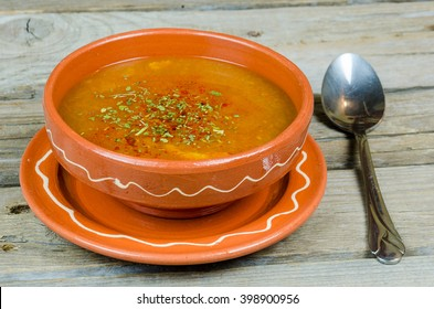 fish soup into a clay plate at wooden board or table