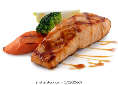 fish steak with broccoli carrots and lemons on a white background