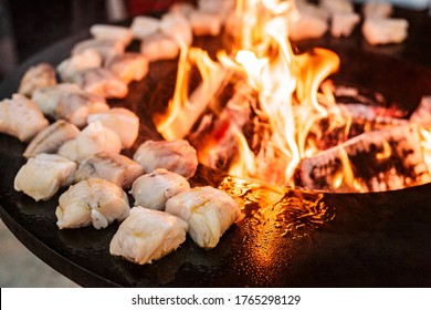 Fish steaks are grilled. Close-up of pieces of fish. Round grill bowl, round roaster with a fire in the center.