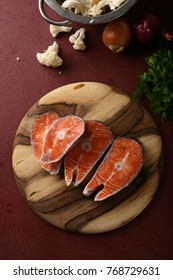 Fish steaks on wood chopping board, food above