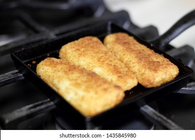 Fish sticks baked on a raclette pan resting on the stove top.