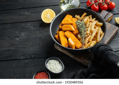 Fish Sticks with vegetables set, on frying iron pan, on black wooden table background , with copyspace and space for text