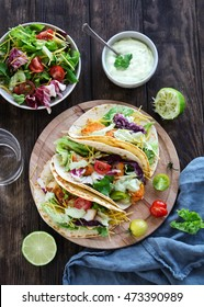 Fish tacos with salad and yogurt sauce on a wooden background, overhead shot