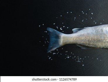 Fish tail concept image on black stone table from top view. Seafood meal presentation on black background This fish is with salt