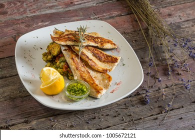 Fish trout. Portion Smoked fillet trout with vegetable dill and lemon. Fish with vegetable salad on plate in hotel or restaurant. On a wooden background. Top view. rustic food