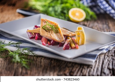Fish trout. Portion Smoked fillet trout with vegetable dill and lemon. Fish with vegetable salad on plate in hotel or restaurant.