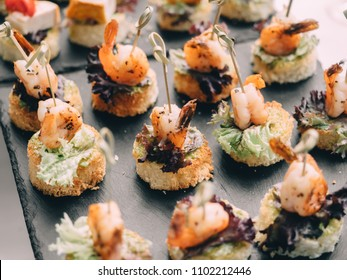 Fish, vegetable canapes on festival wedding table outdoor. Catering service.