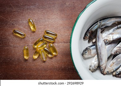 fish in white enamel bowl iron and vitamins omega three on a brown wooden table