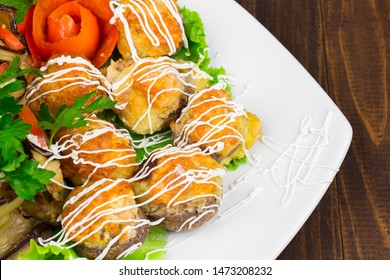 fishballs and meatballs with eggplant rolls with cottage cheese and tomato, parsley on a white plate on a black background