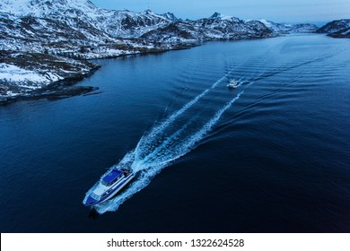 Fisher boat going for fishing before sunrise with mountains full of snow in background. Lofoten Island, Norway.
