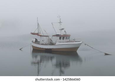 Fisher boat in the heavy fog, Lofoten islands, Norway