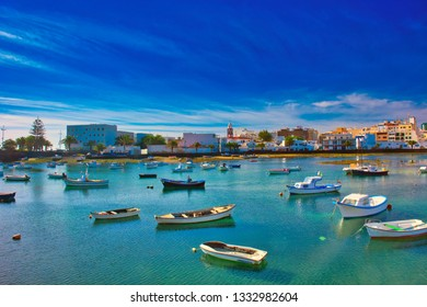 Fisher boats at the laguna Charco de San Gines and the tower of the historic church Iglesia de San Gines at sunshine, city of Arrecife, Lanzarote, Canary Islands