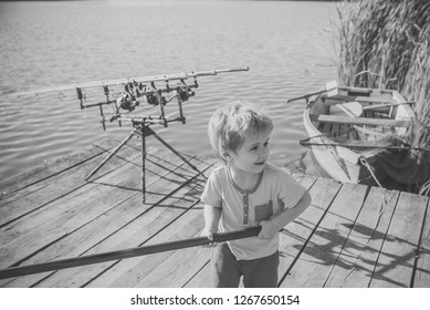 Fisher boy with fishing rod on wooden pier. Fisher child with tackle on river or lake.