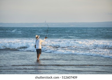 Fisher man with fishing rod on the beach at sunset